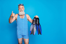 Portrait Of Retired Grandfather With White Hairstyle Holding Diving Equipment Wearing Striped Costume Isolated Over Blue Background