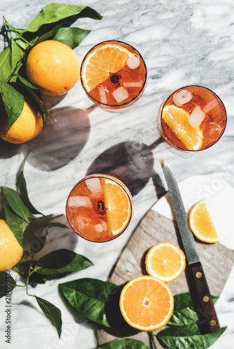 Aperol Spritz aperitif alcohol cold drink in glasses with oranges and ice cubes over grey marble table, top view Canvas Print