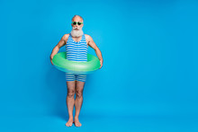Full Body Photo Of Impressed Pensioner In Eyeglasses Eyewear Holding Rubber Ring Wearing Striped Bathing Suit Isolated Over Blue Background