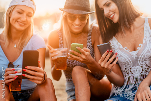 Close up of women drinking beer and using mobile phone at music festival - 285001627