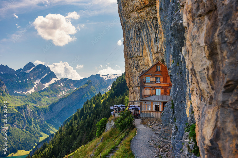 Fototapeta Swiss Alps and a restaurant under a cliff on mountain Ebenalp in Switzerland