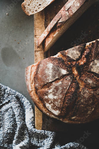 Fototapeta Flat-lay of freshly baked sourdough bread loaf and slices on wooden board over g