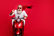 Portrait of funky pensioner in eyewear eyeglasses showing rock-and-roll sign driving bike wearing white jumper isolated over red background