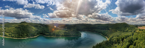 Foto auf Gartenposter Landschaft Camera flies over the Hennesee near Meschede and takes a wide view picture. You can see a ship, hills and forests, sunbeams and lens flares. Gorgeous nature in the Sauerland.