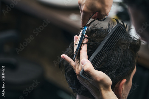 Obraz Barbershop. Close-up of man haircut, master does the hair styling in barber shop. Close-up, master Barber does the hairstyle and styling with scissors. Concept Barbershop. - fototapety do salonu