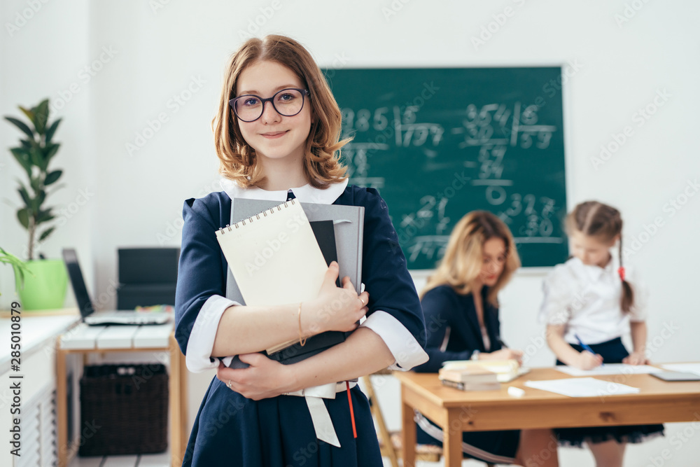 Fototapety, obrazy: Portrait of smiling school girl with books in classroom