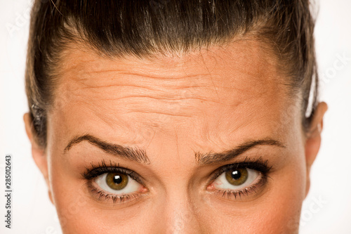 young woman showing her forehead wrinkles with her fingers on a white background Fototapet