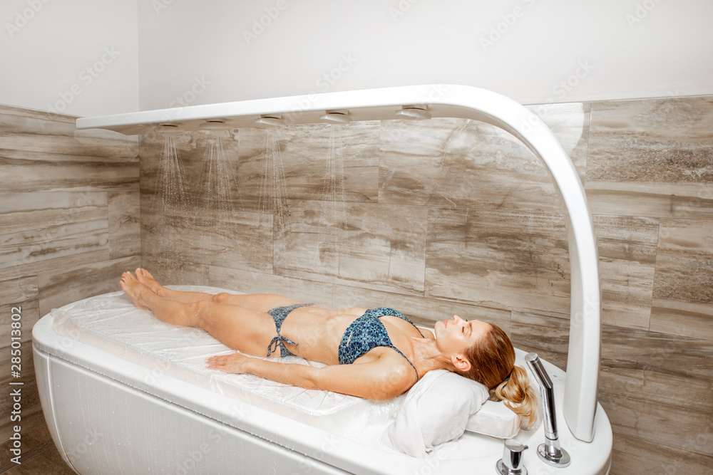 Fototapeta Woman lying under the hot shower in the spa