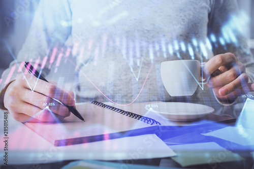 Fototapeta Forex chart hologram on hand taking notes background. Concept of analysis. Double exposure obraz na płótnie