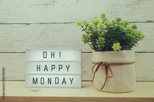 Fotografia  Happy Monday lightbox alphabet wording on wooden background