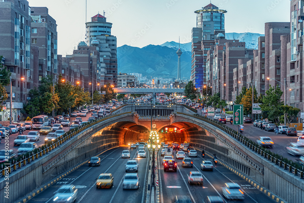 Fototapety, obrazy: 06/05/2019 Tehran,Iran,Famous night view of Tehran,Flow of traffic round Tohid Tunnel with Milad Tower and Alborz Mountains in Background, Tohid Tunnel one of longest urban tunnel in Middle East