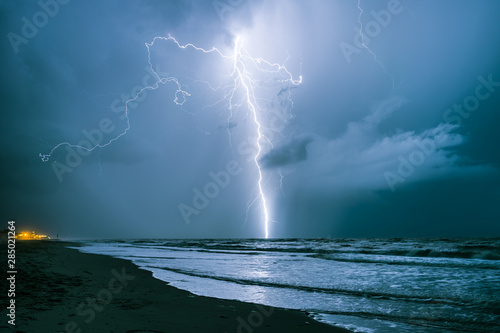 Staande foto Noord Europa Bright lightning bolt strikes in the North Sea during a summer thunderstorm
