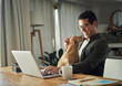 Cheerful man playing with dog while using laptop