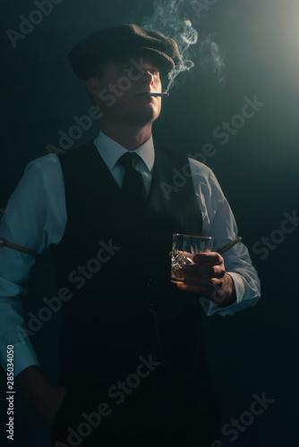 Retro businessman with cap smokes cigarette in smoky room. Tablou Canvas