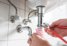 Man Repairing Sink Trap With Adjustable Pipe Wrench In Bathroom