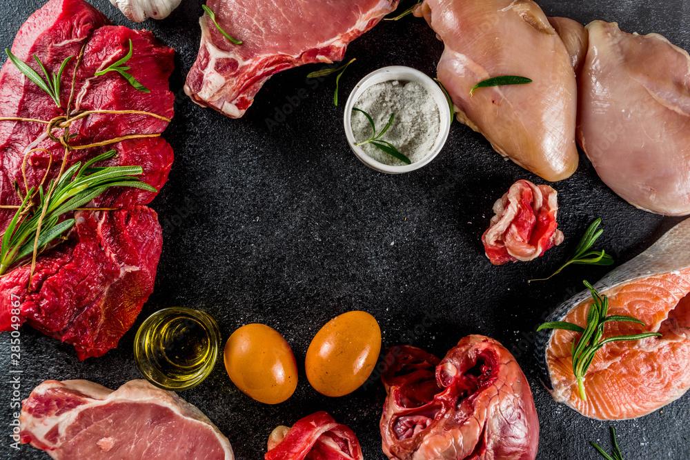 Fototapeta Carnivore diet background. Non vegan protein sources, Different meat food - chicken breast, pork steak, beef tenderloin, eggs, spices for cooking. Black stone concrete background copy space