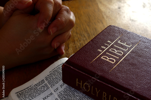 Holy Bible on a table and hands in praying position