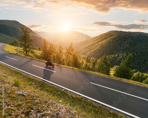 Motorcycle driver riding in Alpine landscape. Canvas Print