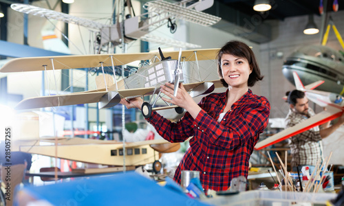 Smiling woman showing sports biplane model she created in aircraft workshop