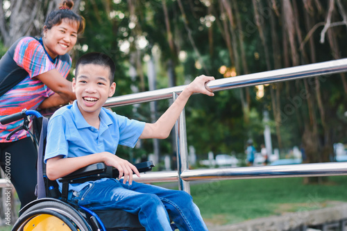 Disabled child on wheelchair is play and learn in the outdoor park like other people, He has adult care and love, Life in the education age of special children, Happy disability kid concept Tablou Canvas