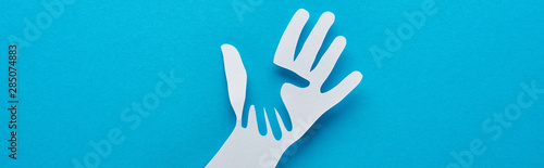 Photo top view of paper cut parent and child hands on blue background, panoramic shot