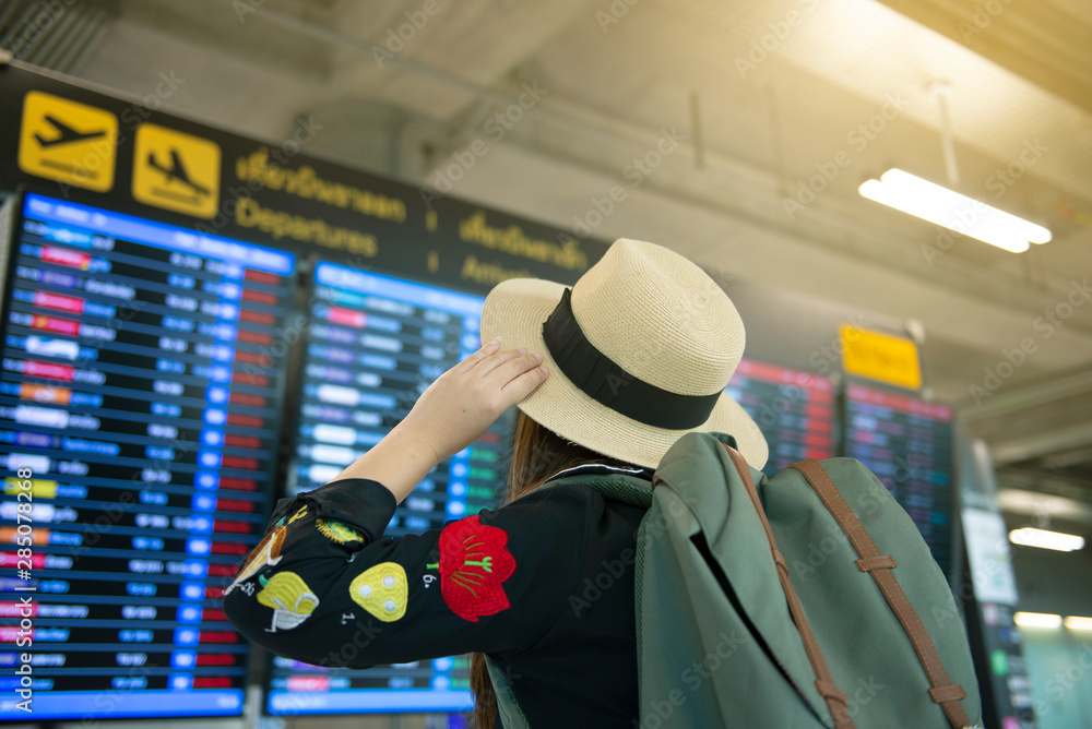 Fototapety, obrazy: Tourist woman is checking flight schedule at the airport with worry delay feeling acting.