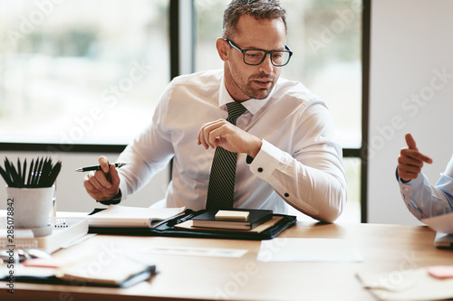 Mature businessman going over paperwork during a boardroom meeti