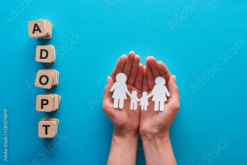 cropped view of woman holding paper cut lesbian family near blocks with adopt le Canvas Print