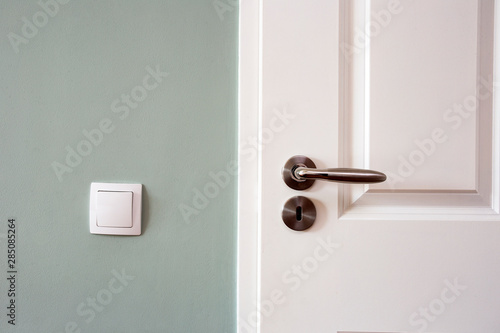 Fototapeta Modern white door with chrome door handle and light switch, new clean design obraz