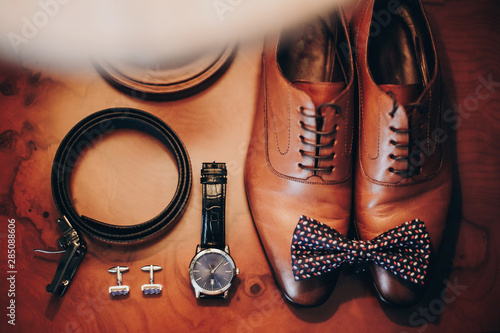 Fotografía  Stylish watch, expensive, shoes, bow tie, cufflinks and belt for groom on wooden table in hotel room