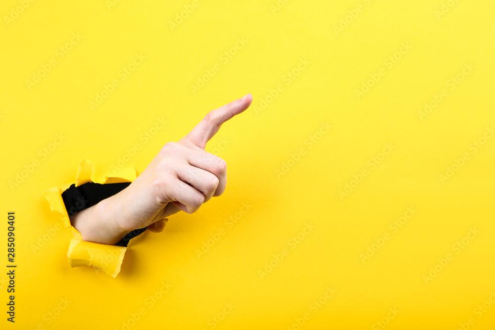 Fototapeta Hand from yellow torn paper