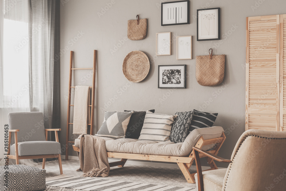 Fototapeta Beige scandinavian settee with patterned pillows in stylish living room interior