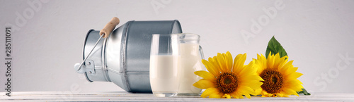 Fototapeta A jug of milk and glass of milk on a wooden table and flower obraz