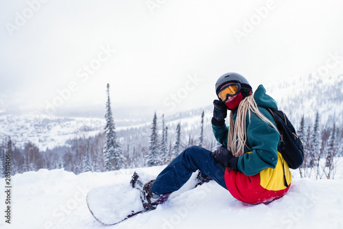 Fotomural Girl freerider with snowboard in the mountains sitting on a snowy slope
