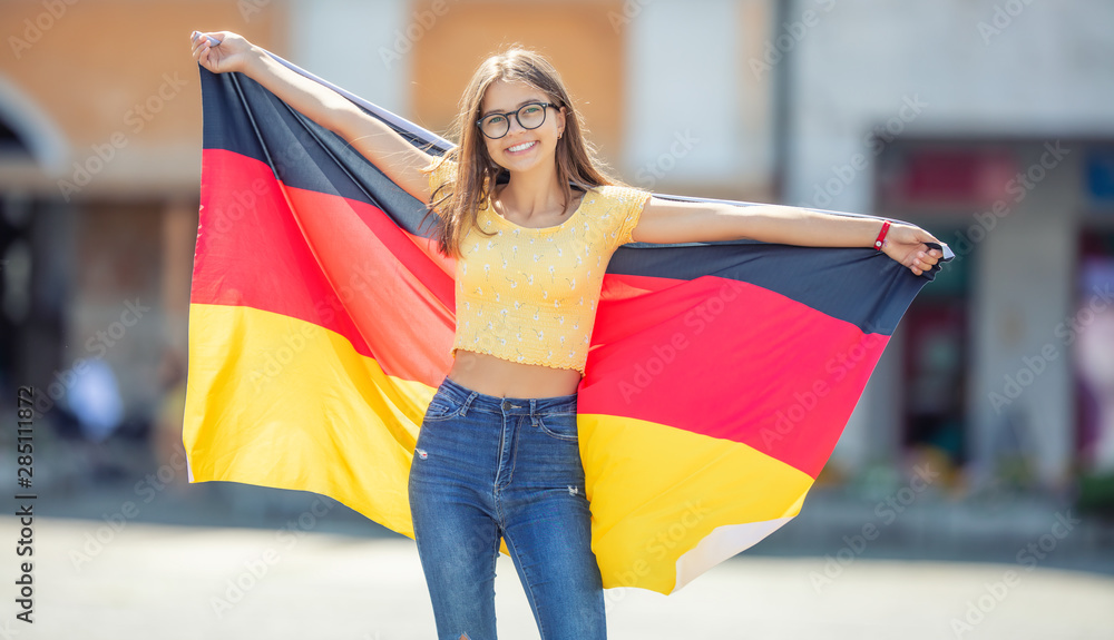 Fototapeta Attractive happy young girl with the germany flag
