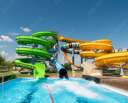 Fototapeta Water park, bright multi-colored slides with a pool. A water park without people on a summer day with a beautiful, cloudy blue sky obraz na płótnie