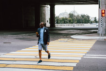 Black Man With Smartphone Crossing Road