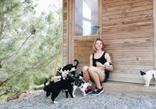 Smiling Woman With Plenty Of Cats Outdoors