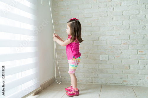 Fotografiet  Little Toddler Opening Window In Living Room