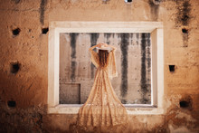 Back View Of Gorgeous Woman In Beige Lace Dress Standing On Wall Of Deserted Building And Holding Hat
