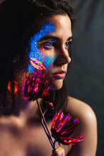 Portrait Of Beautiful Young Woman Covered With Luminous Paint On Face Holding A Flower And Looking Away.