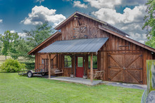 Rustic Barn With Metal Roof And Puffy Clouds