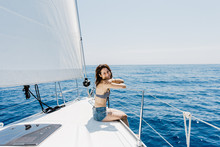 Side View Of Traveling Woman Wearing Swimsuit Sitting On Side Of Yacht In Sea Looking At Camera