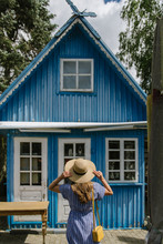 Back View Of Woman In Straw Hat And Sundress Standing In Front Of Colourful Blue Summer House In Daylight