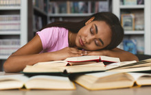 Tired Girl Napping On Books Stack In Library