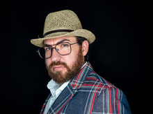 Handsome Bearded Man In Glasses And Looking At Camera On Black Background