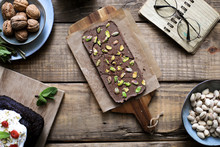 From Above Served Tasty Chocolate Dessert Garnished With Pistachios On Baking Paper On Wooden Table