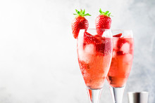 Rossini - Italian Alcoholic Cocktail With Sparkling Wine, Fresh Strawberry Puree And Ice In Champagne Glasses, Copy Space, Selective Focus