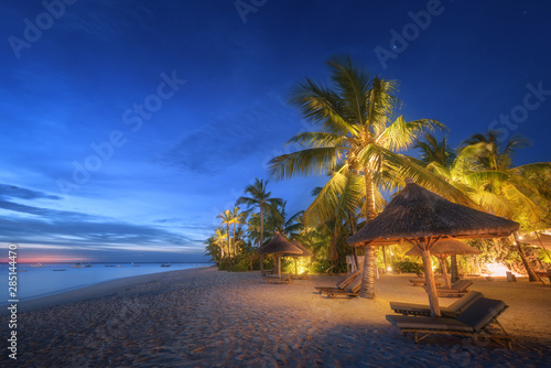 Cadres-photo bureau Palmier Sandy beach with palm trees and sunbeds under umbrellas during blue hour in summer. Landscape with sea shore, beautiful starry sky, green palms and yellow light at night. Travel in Zanzibar, Africa