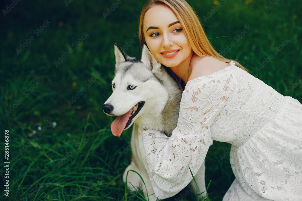 Fototapety, obrazy: Beautiful and gentle girl with light hair dressed in white dress is playing along with her sweet doggy in summer green park.